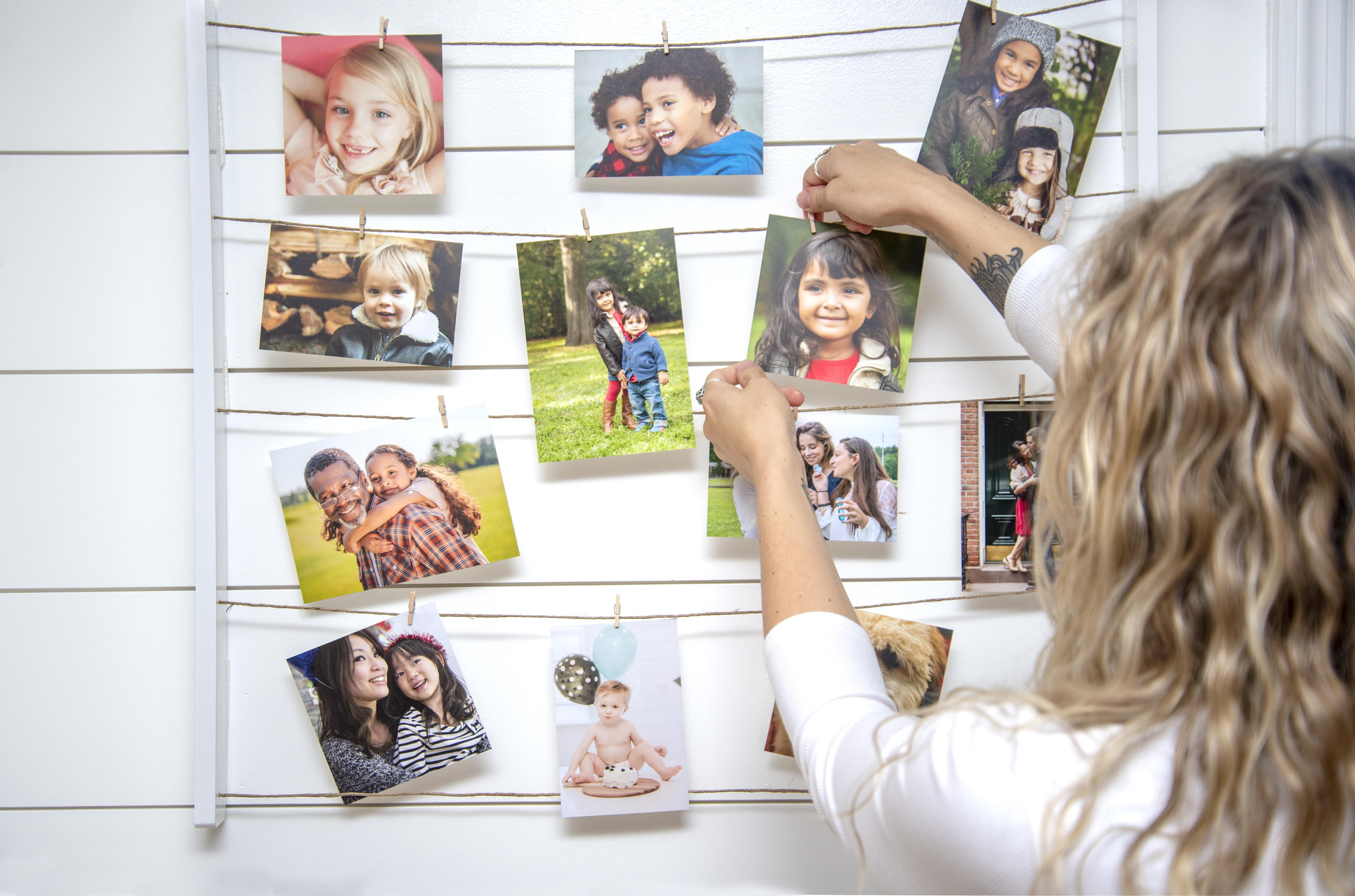 Adult female pinning a photo of a young girl along a string holding many other photos against a white wall.