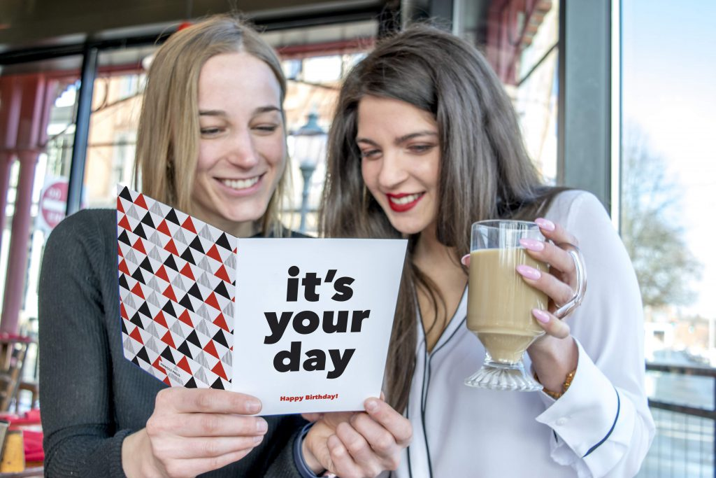 Blonde adult female holding a greeting card; a brunette adult female holding a glass coffee cup stands next to the blonde as they both look over the greeting card