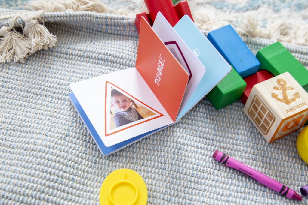 Small board book with pages fanned open to show a photo of a little boy on the left and multi-colored pages on the right. There are wood blocks and crayons around the book.