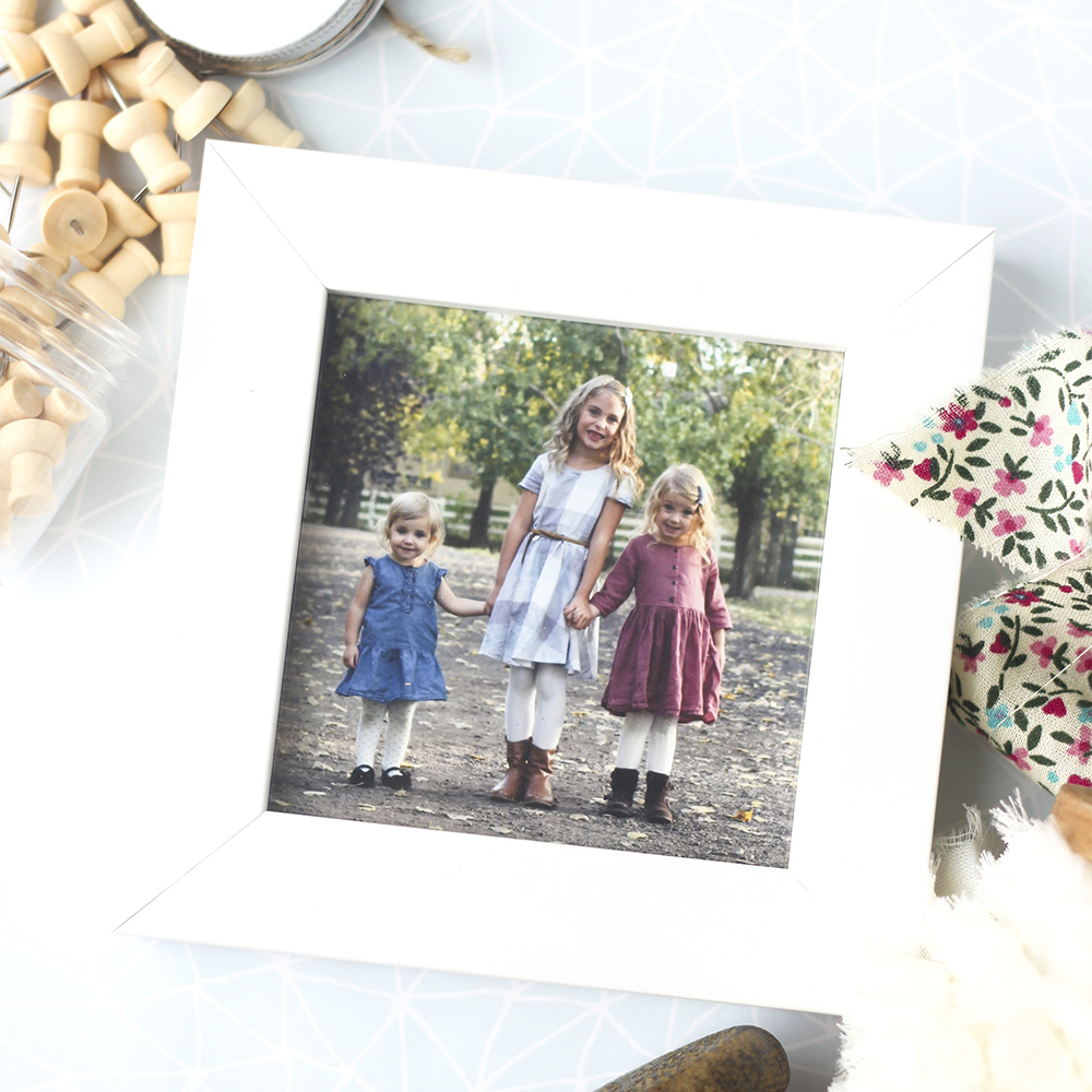 White frame with the photo of three young girls of various ages holding hands outdoors.