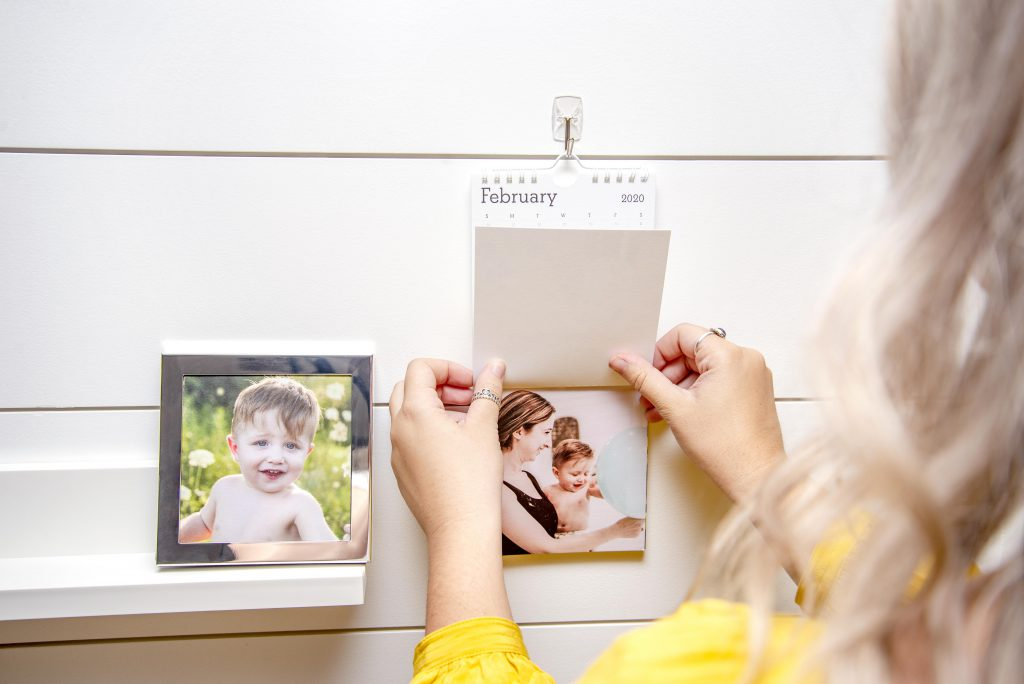 Adult blonde female shown holding the page of a hanging wall photo calendar. Silver frame with the photo of a baby boy shown on a shelf next to the calendar.