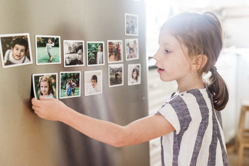 Young brunette girl holding a magnet up to the front of a stainless steel refrigerator door where there are a set of photo magnets