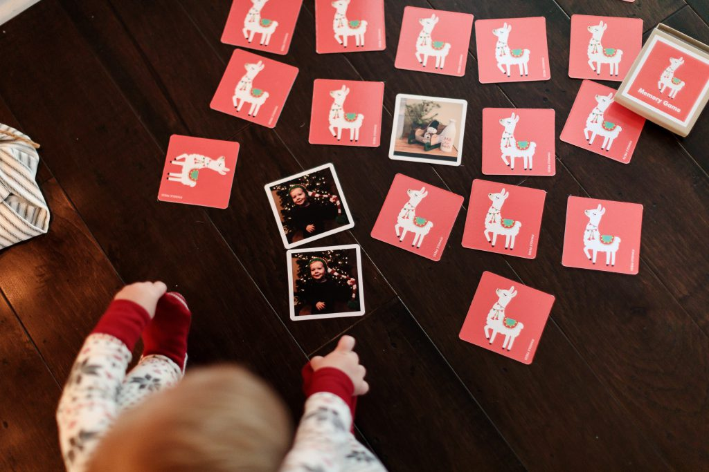 baby sitting with a deck of cards showing matching photos and llamas