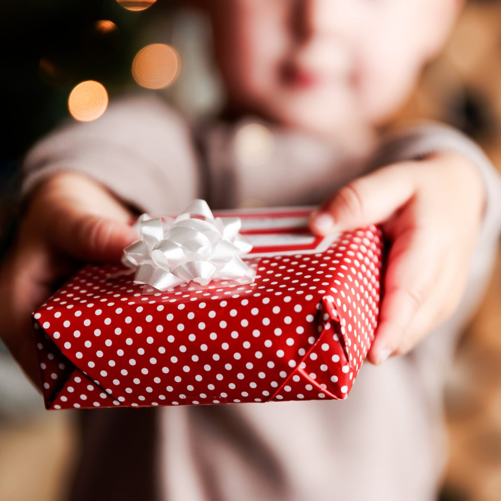 blurred outline of small boy, in focus are his two hands holding small box wrapped in red paper with white polka dots and white bow