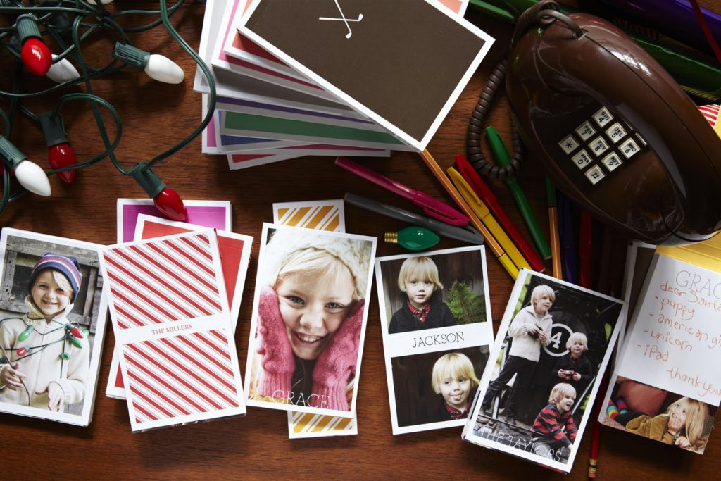 Several notepads stacked on tabletop featuring faces of children smiling