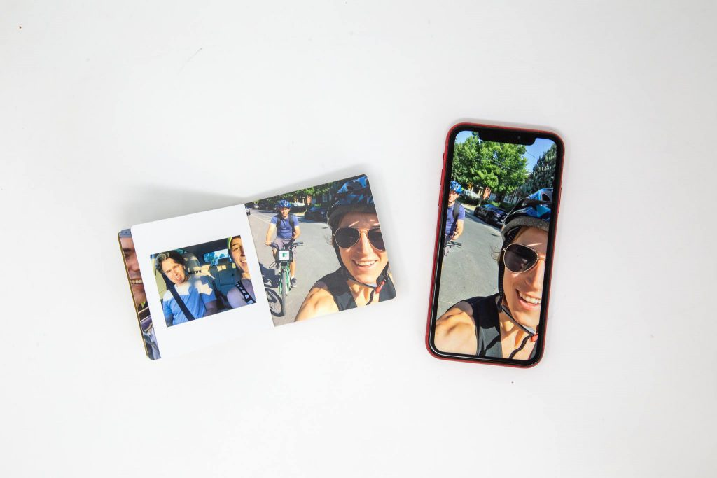 Mini photo book opened to display two photo pages. Mobile phone next to book displaying the same photo as printed on one page.
